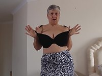Short haired mature amateur British granny Savana strips at home